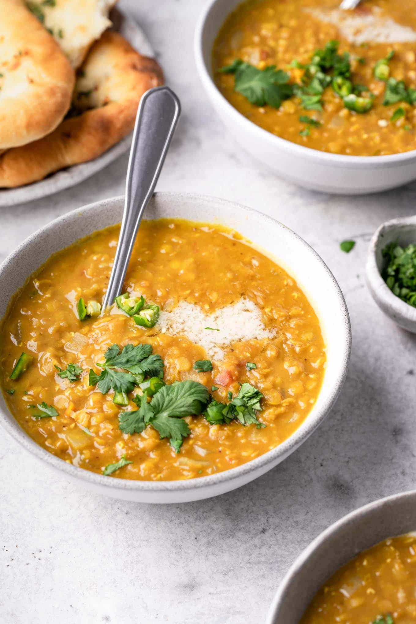 tamarind red lentil soup served in bowls with garlic naan