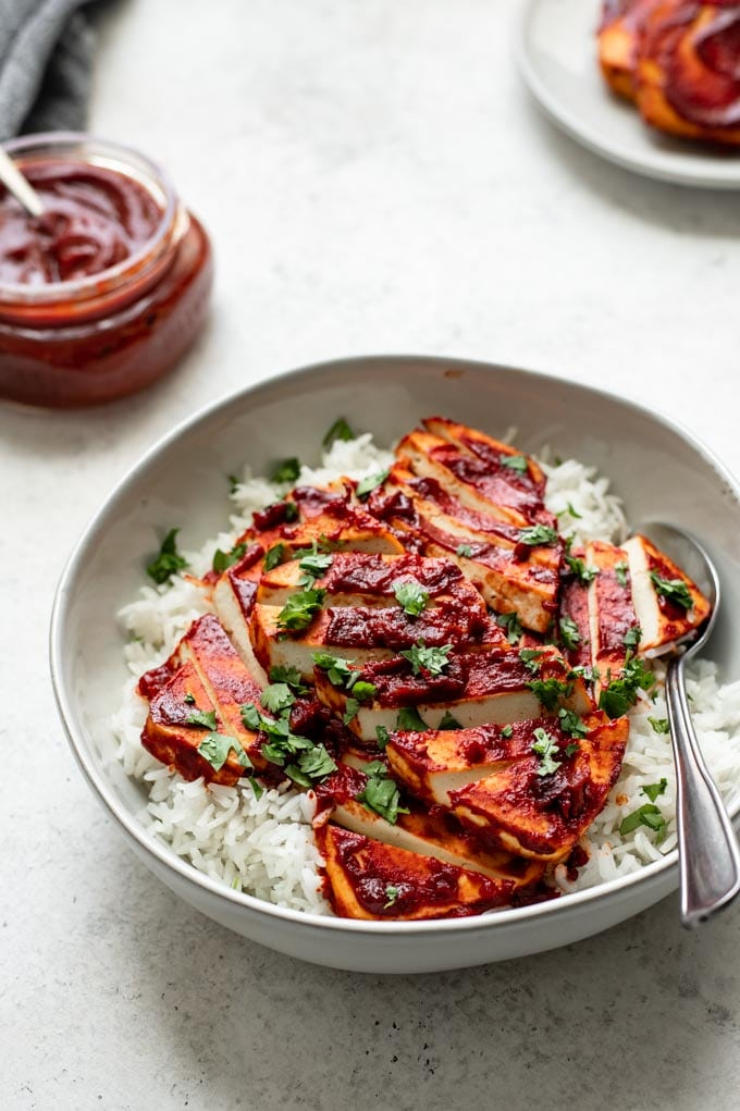 side view of a bowl of barbecue tofu over rice, garnished with cilantro. A jar of barbecue sauce is in the background as well as a few slices of barbecue baked tofu on a plate