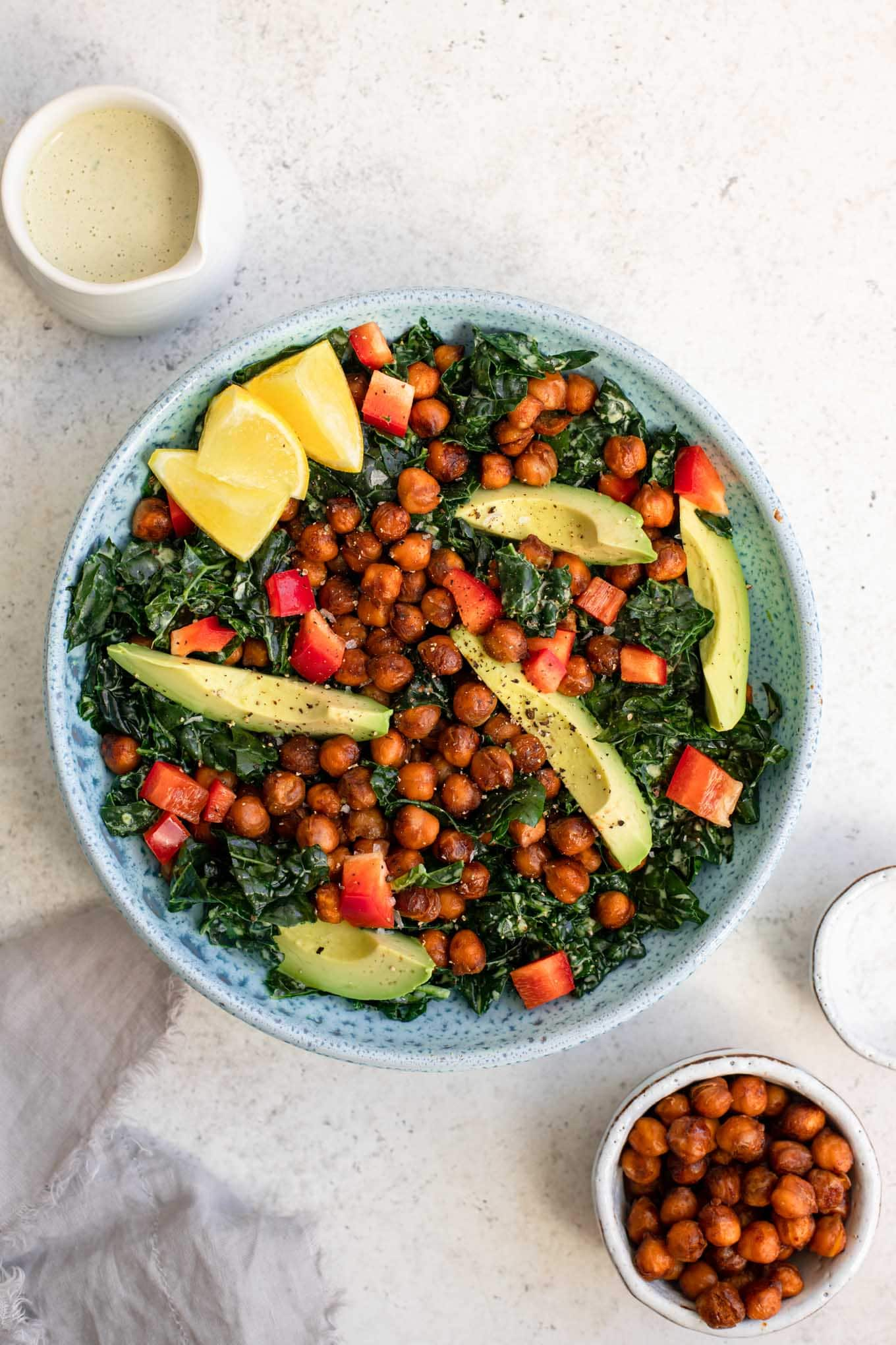 kale salad with smoky chickpeas and avocado in a bowl with lemon wedges and a side of dressing