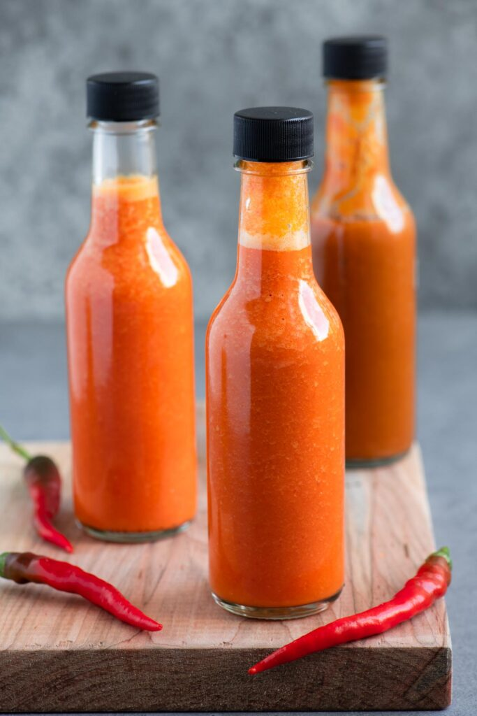 bottled homemade hot sauce on a cutting board with 3 red chilies
