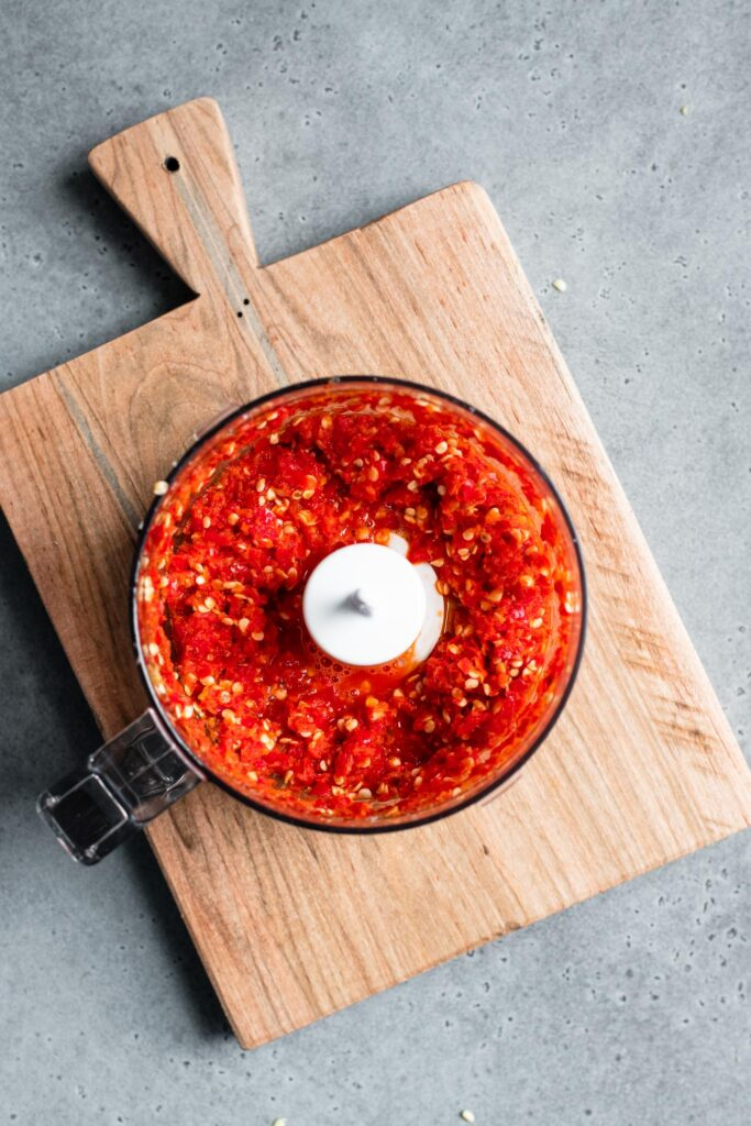 chili's chopped in mini-food processor sitting on a cutting board