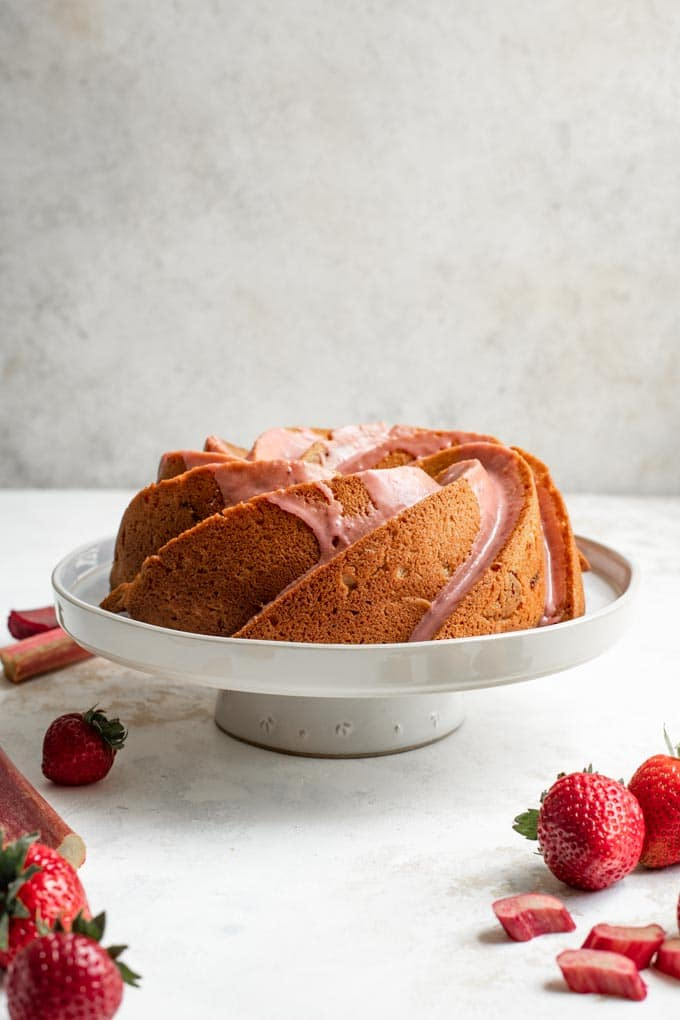 almond rhubarb bundt cake with a strawberry rhubarb glaze on a stand with strawberries and rhubarb surrounding it