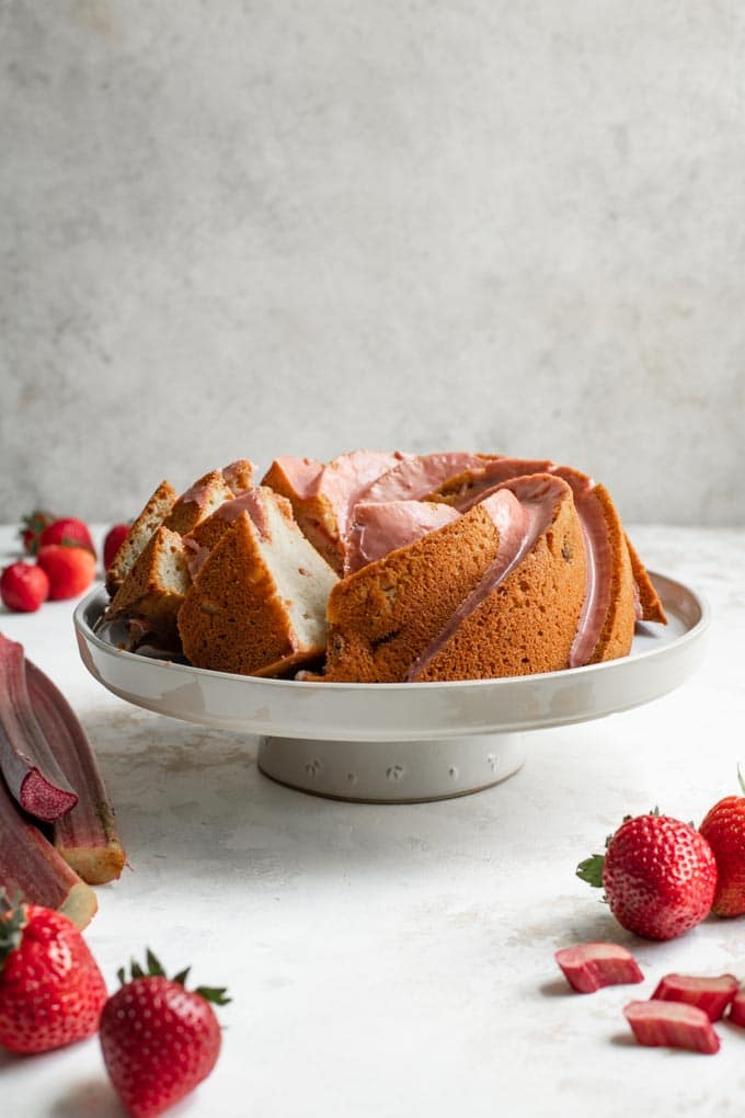 straight on shot of the almond rhubarb bundt cake with some slices cut and set at an angle so you can see the soft texture
