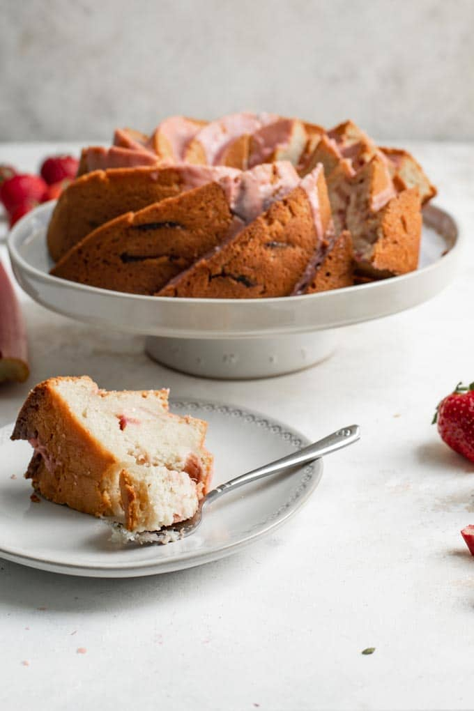 a close up of a slice of the almond rhubarb bundt cake with a forkful cut off the slice and the rest of the cake in the background
