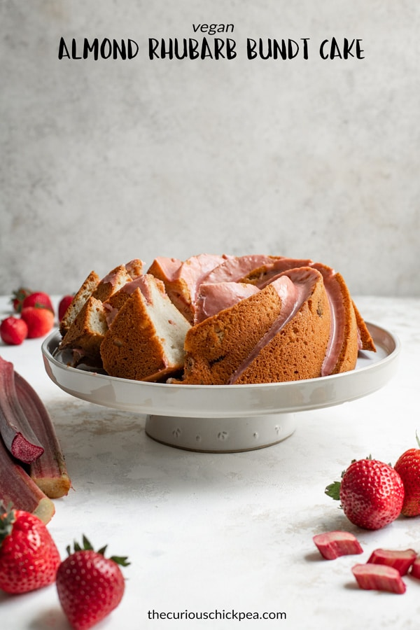 The softest almond cake is studded with fresh rhubarb and finished with a strawberry rhubarb glaze in this beautiful vegan dessert. It's so delicious and perfect for spring! | thecuriouschickpea.com #vegan #vegandessert #vegancake #almondcake