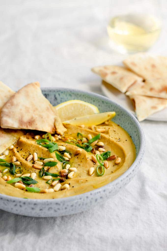 side view of the creamy favosalata with pine nuts and scallions for garnish and a plate of naan for dipping