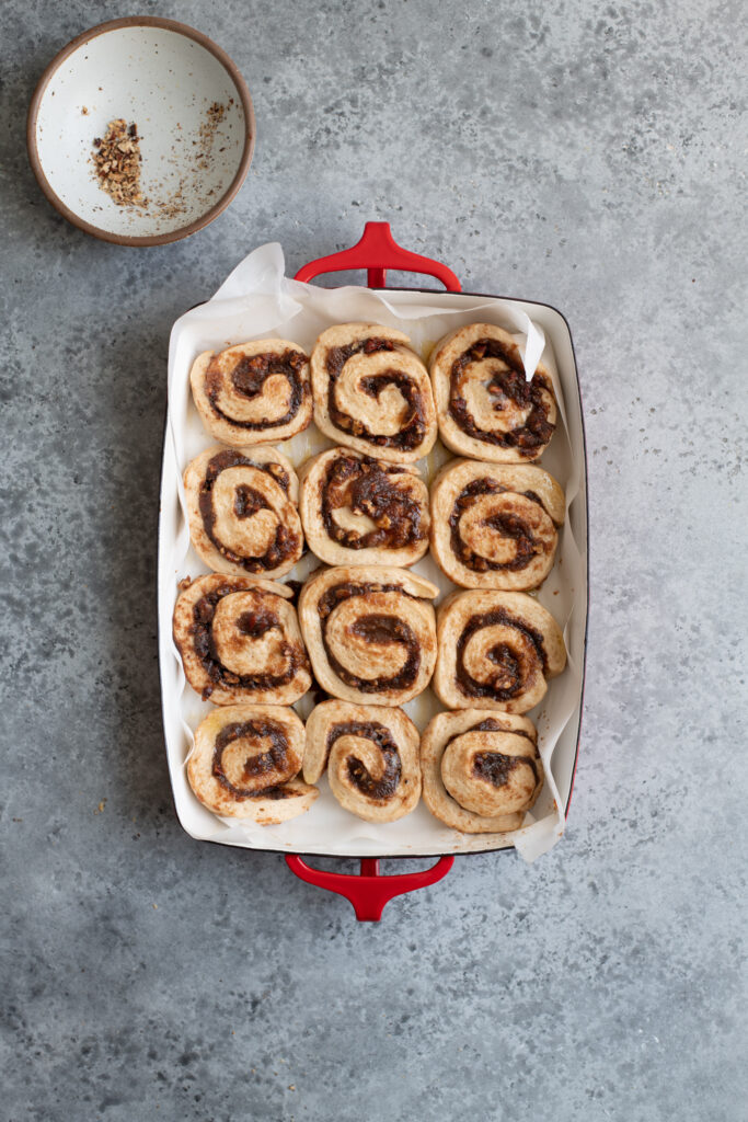 cinnamon rolls in baking dish after rising and before baking