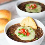 black bean soup with pepita cream, garnished with diced cherry tomatoes and chives and served with sweet potato rolls