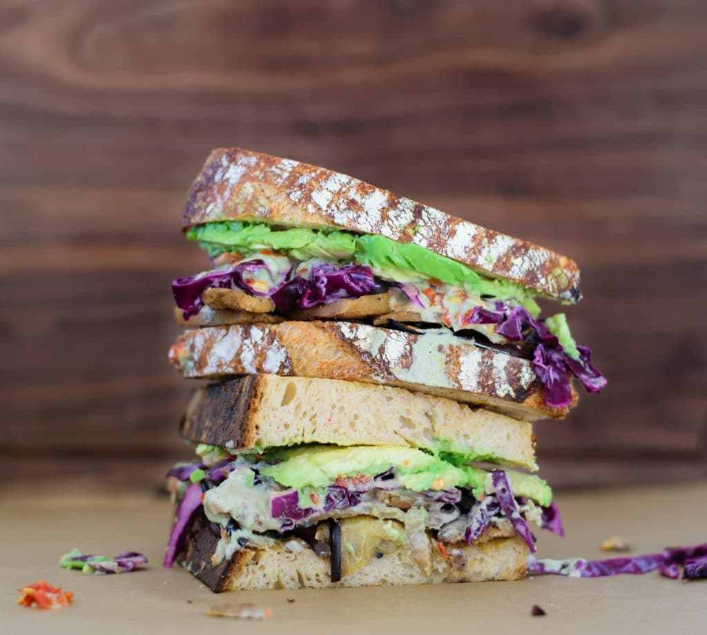 sandwich with madras marinated eggplant, seitan, cabbage slaw, pepita cream, chile sauce, and avocado on homemade toasted sourdough