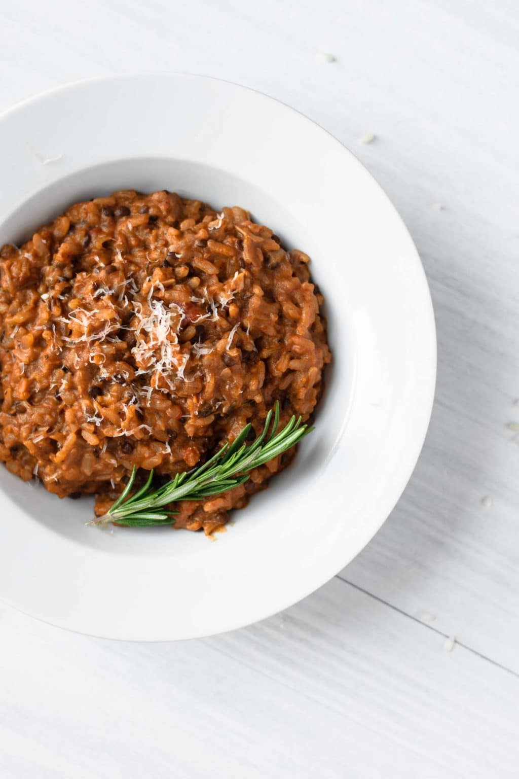 vegan risotto bolognese served with vegan parmesan and fresh rosemary sprig