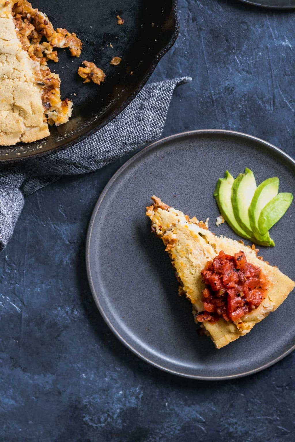 Slice of tamale skillet pie served on a plate with avocado and some tomato salsa