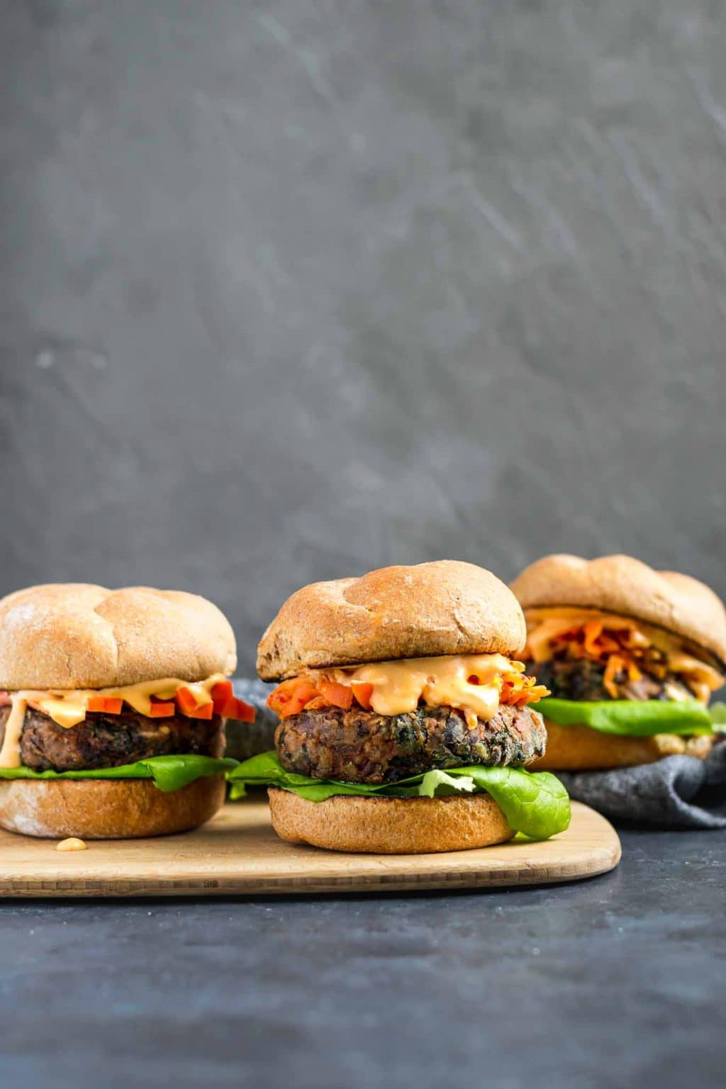 Vegan gochujang bean burgers topped with kimchi, fermented carrots, and gochujang mayo.