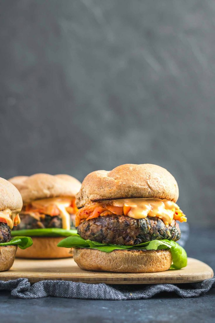 Vegan Gochujang Bean Burgers   Spicy and ultra flavorful black bean and kidney burgers are given a Korean twist using gochujang (a fermented savory and sweet Korean chili paste). Topped with kimchi or fermented vegetables and a gochujang mayo, these easy vegan burgers make the perfect meal!   thecuriouschickpea.com #vegan #gochujang #veganburgers