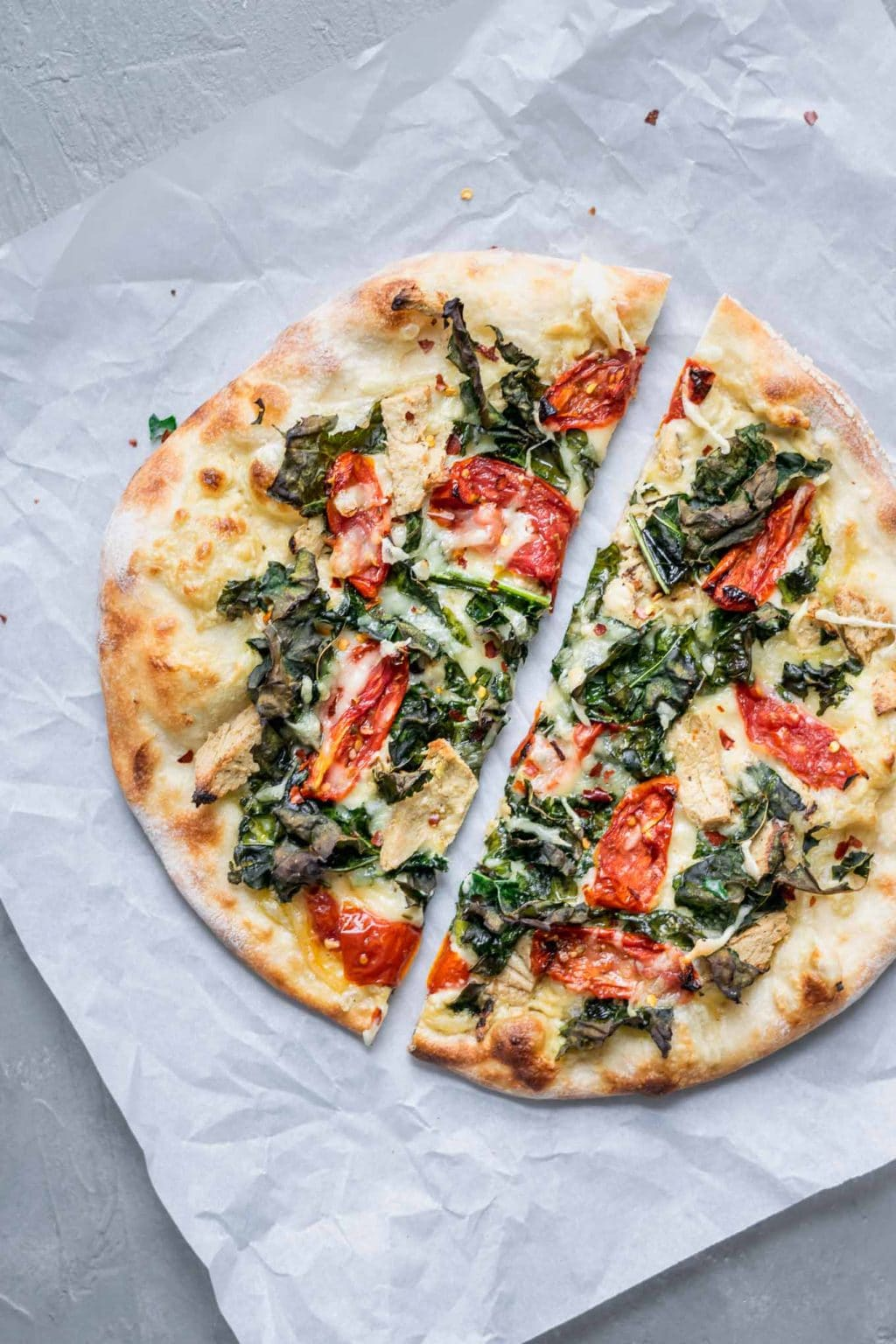 Crispy kale, roasted tomato, and vegan chicken white sauce pizza cut in half