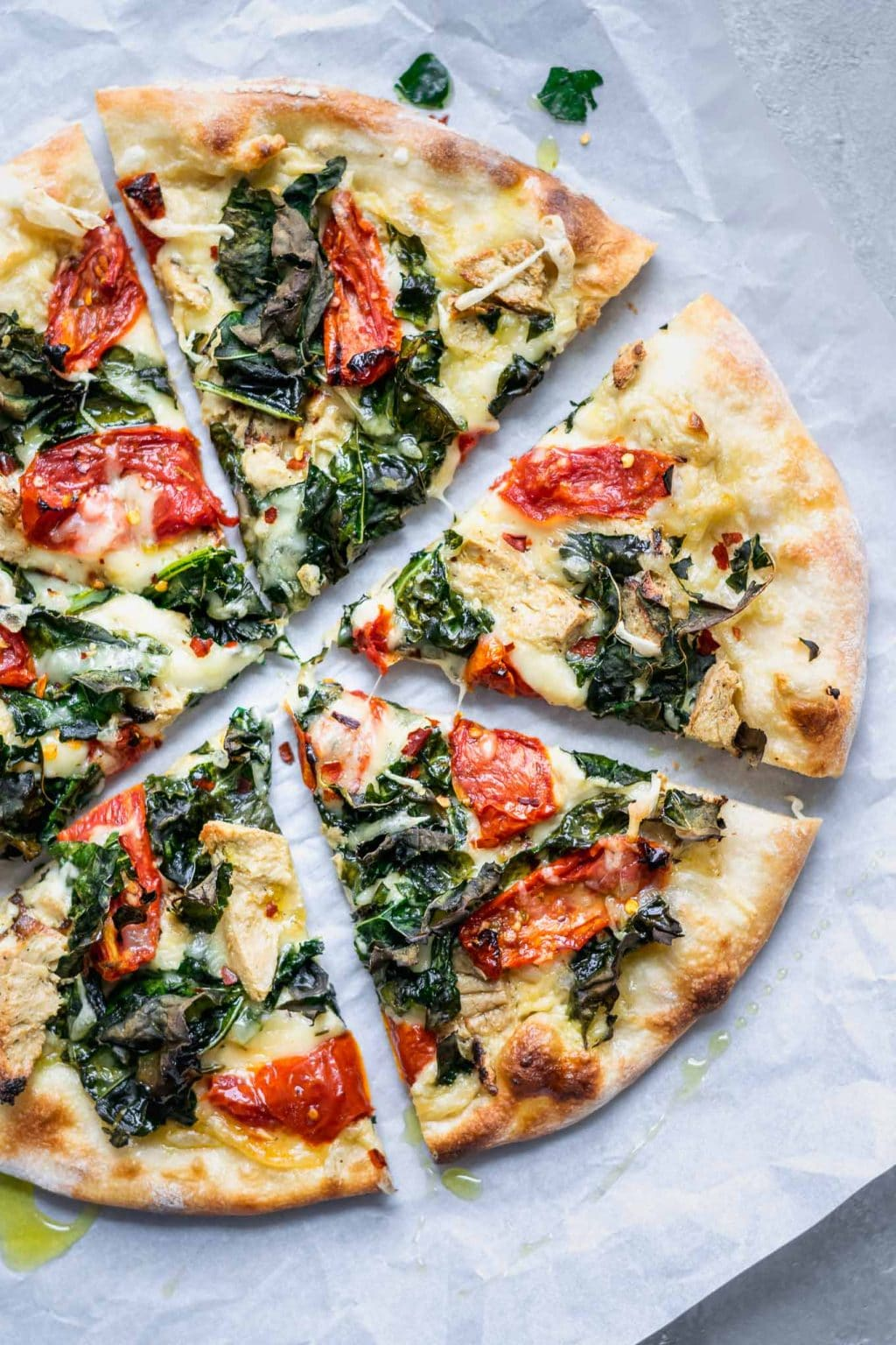 Sliced Crispy Kale, Roasted Tomato, and Vegan Chicken White Sauce Pizza