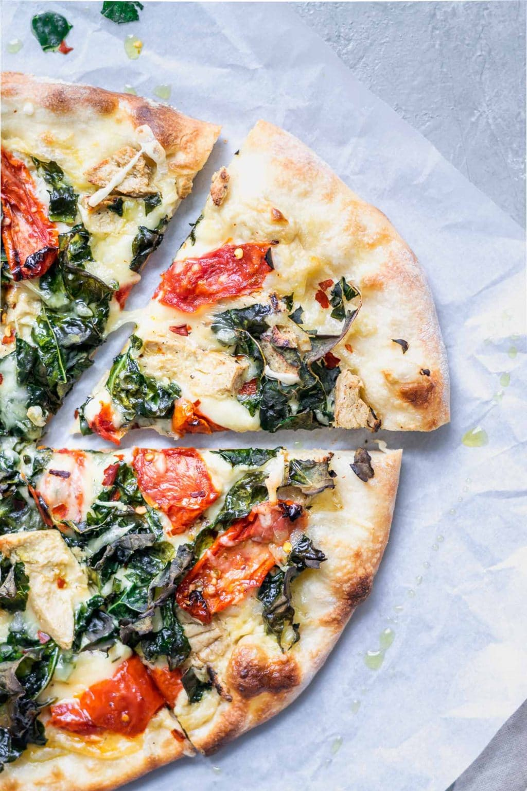 Slice of crispy kale, roasted tomato, and vegan chicken white sauce pizza