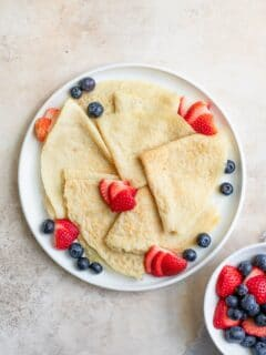 vegan crepes folded into quarters and served with fresh sliced strawberries and blueberries