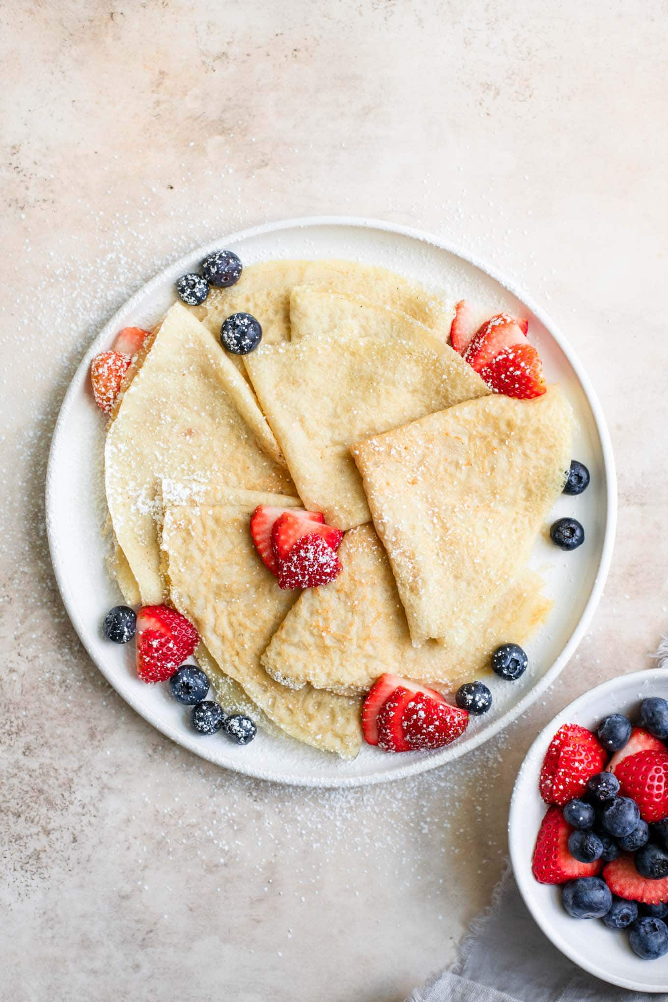 vegan crepes served with fresh fruit and powdered sugar
