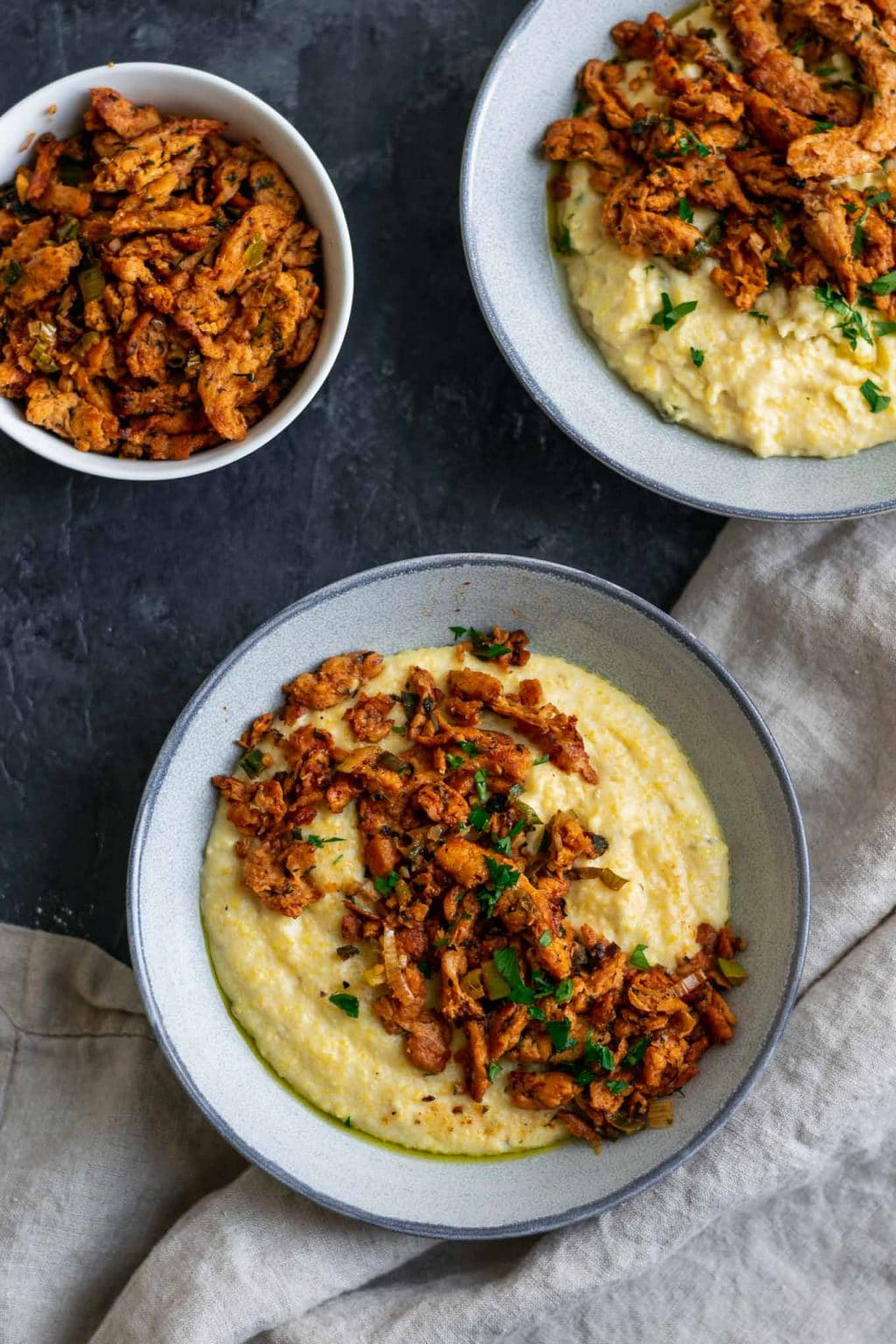 Cajun soy curls and creamy vegan jalapeño grits, two servings with an extra bowl of cajun soy curls