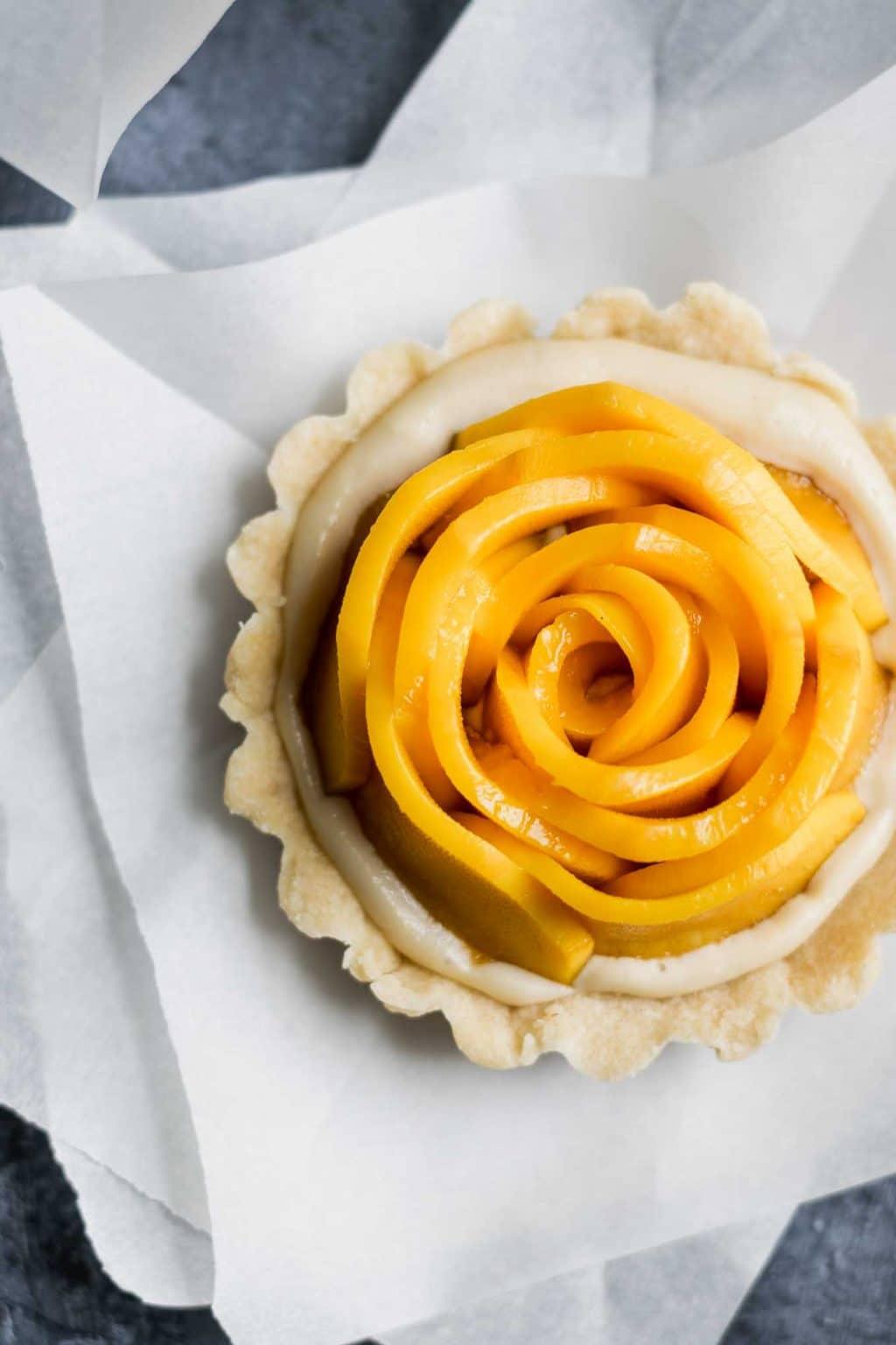 vegan mango tarts with vanilla pastry cream and shortbread crust. Mangoes are cut into rosettes.