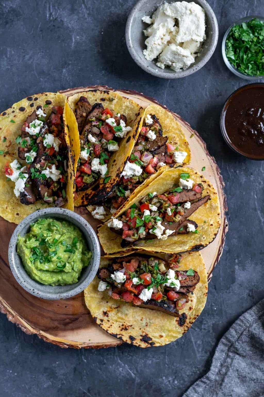Vegan seitan carne asada tacos topped with pico de gallo and vegan queso fresco with guacamole and extra marinade, queso fresco, and cilantro to serve. 5 tacos assembled on a platter.