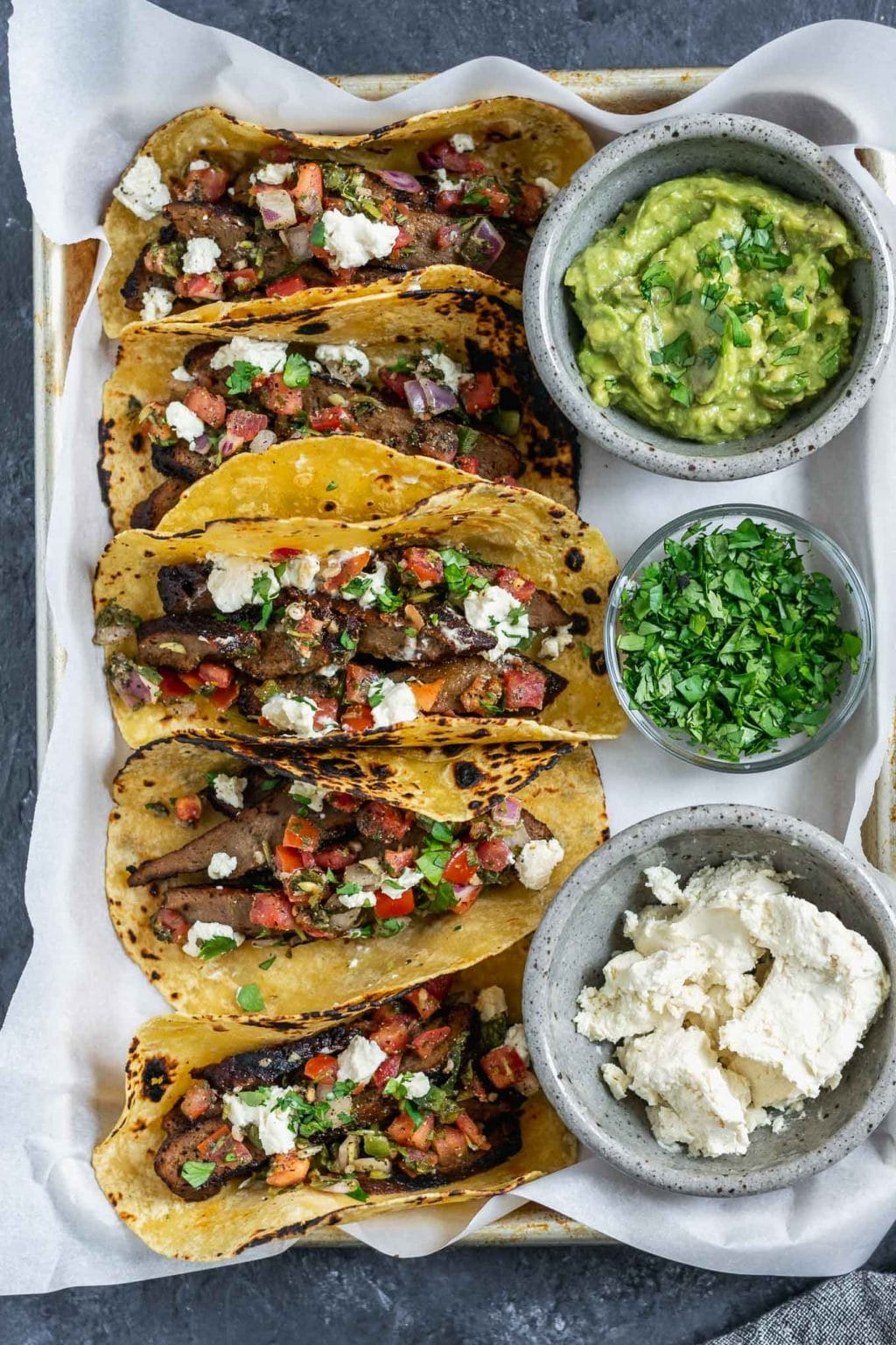 Vegan seitan carne asada tacos topped with pico de gallo and vegan queso fresco with guacamole, queso fresco, and cilantro to serve. 5 tacos assembled on a tray.