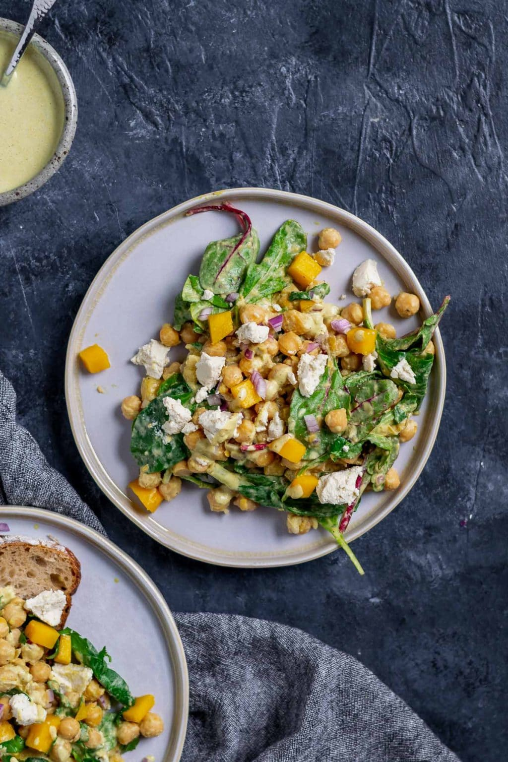 Curried chickpea and mango salad with vegan queso fresco. Extra dressing in a bowl in top corner and a second plate of the salad with a slice of toast