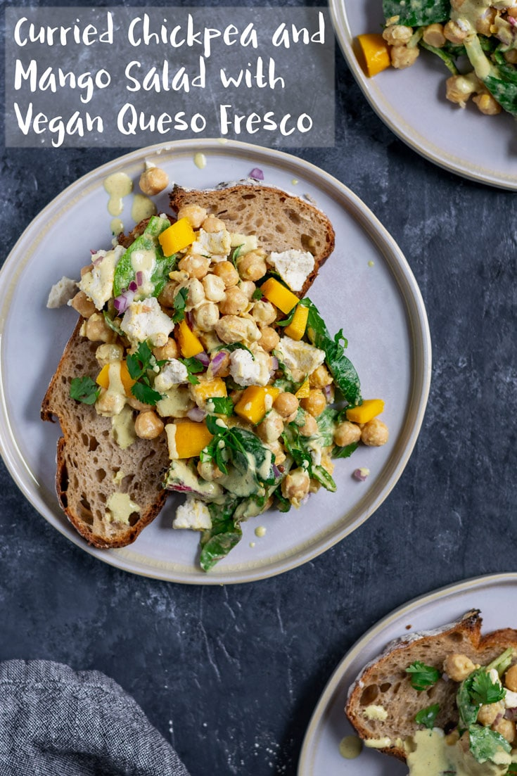 Chickpeas and ripe mango are tossed in a creamy curry dressing along with some baby greens and vegan queso fresco. Perfect for serving alongside some crusty bread, in a sandwich, or as a side salad. | thecuriouschickpea.com #vegan #salad #chickpeas #mango