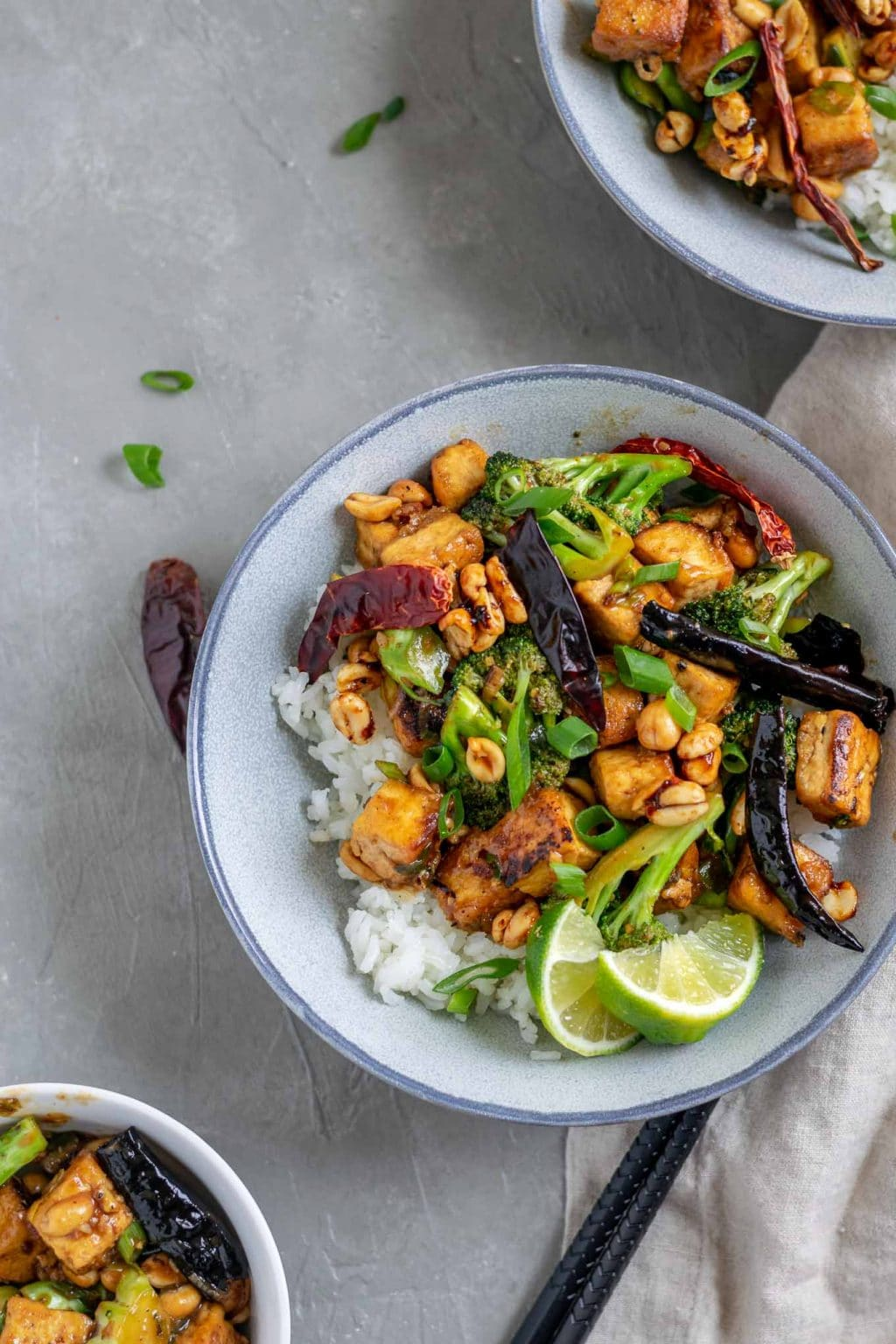 vegan kung pao tofu with broccoli and jasmine rice. Garnished with lime wedges and scallion greens
