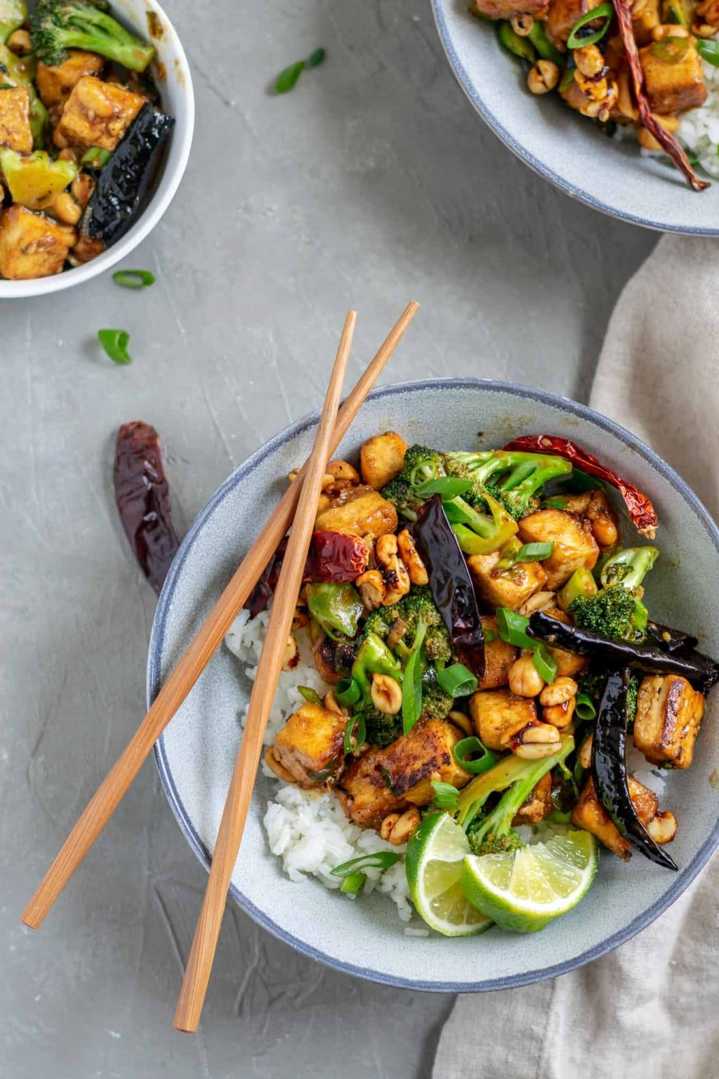 vegan kung pao tofu with broccoli and jasmine rice. Garnished with lime wedges and scallion greens and a pair of chopsticks is set over the bowl