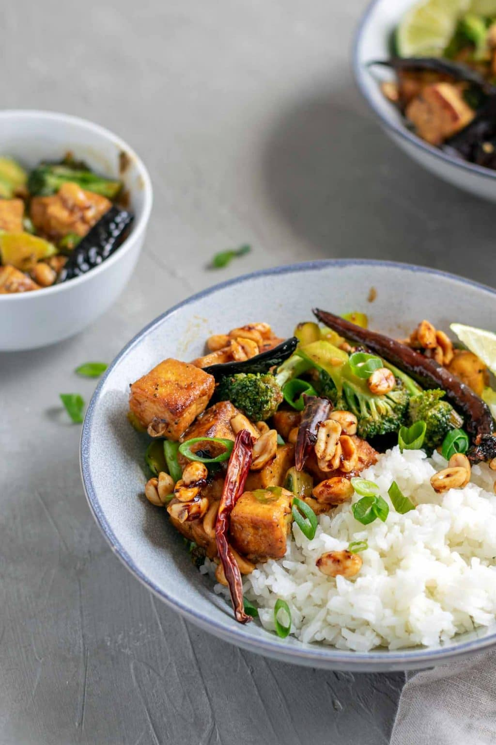 vegan kung pao tofu with broccoli and jasmine rice. Garnished with lime wedges and scallion greens. Angled view.