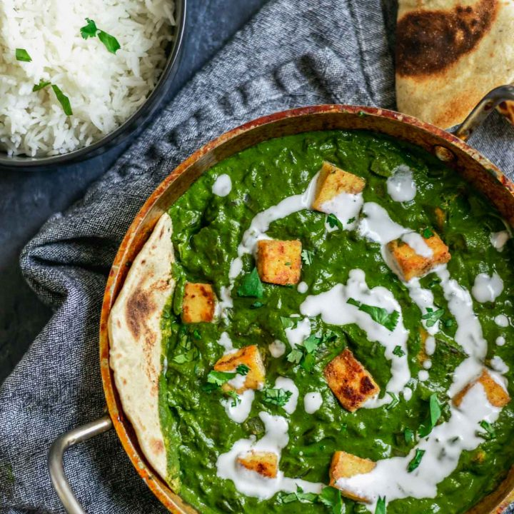 vegan palak tofu paneer with a drizzle of coconut milk and served with fresh chapati bread and basmati rice with extra tofu paneer on the side