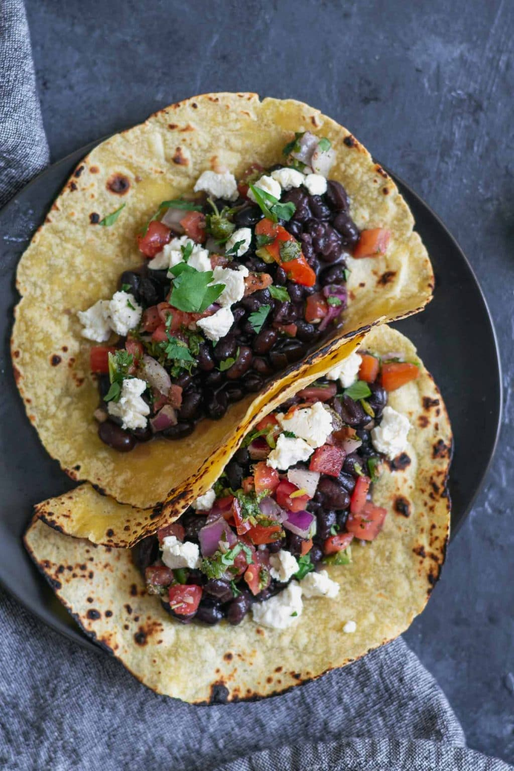 Easy homemade vegan queso fresco on black bean tacos with pico de gallo and charred corn tortillas.