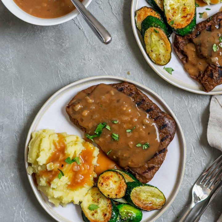 Grilled homemade seitan steaks with mashed potatoes and shallot gravy with sautéed zucchini, garnished with parsley, and extra gravy on the side