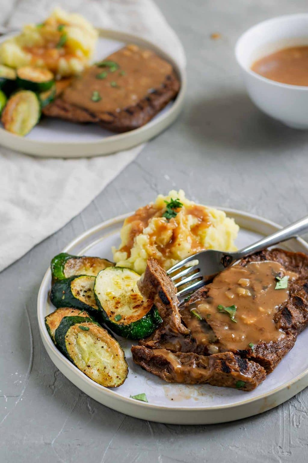 Grilled homemade seitan steaks with mashed potatoes and shallot gravy with a side of zucchini and a garnish of parsley. The steak is cut with one bite on a fork and there is extra gravy served on the side.
