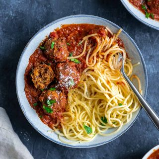 Spaghetti with roasted eggplant marinara and vegan lentil meatballs, one lentil meatball split open to show texture. Garnished with vegan parmesan and minced parsley. With fork twirling spaghetti in the bowl.