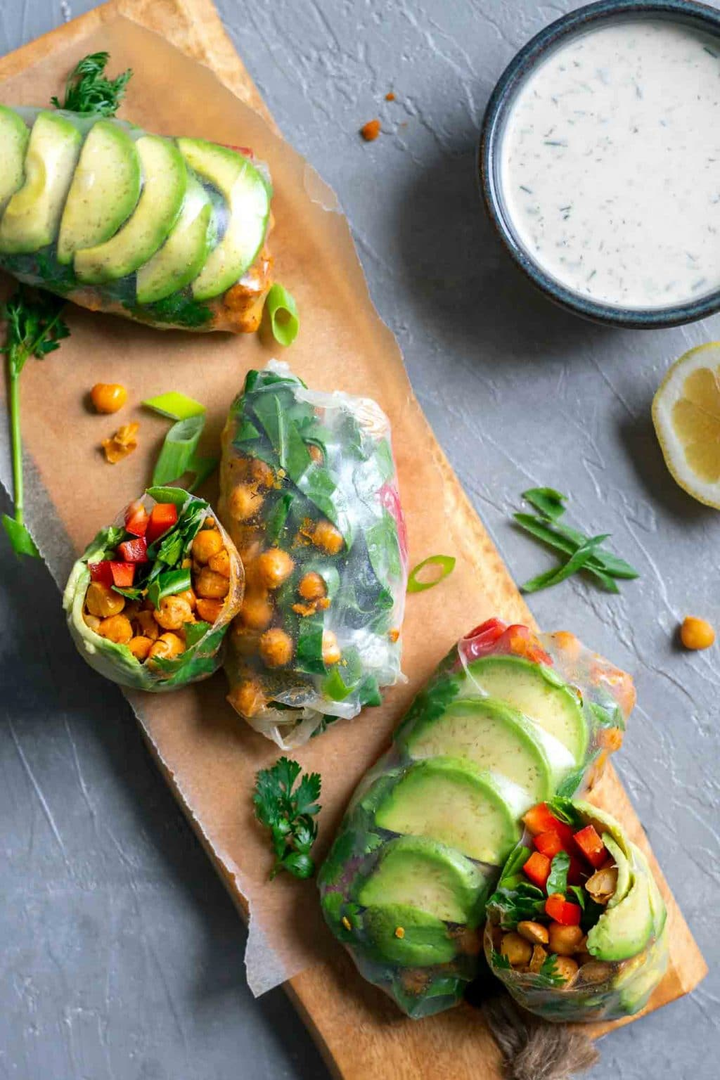 Buffalo chickpea rice paper wraps with tahini ranch dip served on a wooden board with dip in a bowl