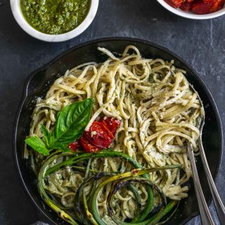 vegan garlic pesto alfredo pasta with grilled garlic scapes and roasted cherry tomatoes served with extra garlic scape pesto and tomatoes