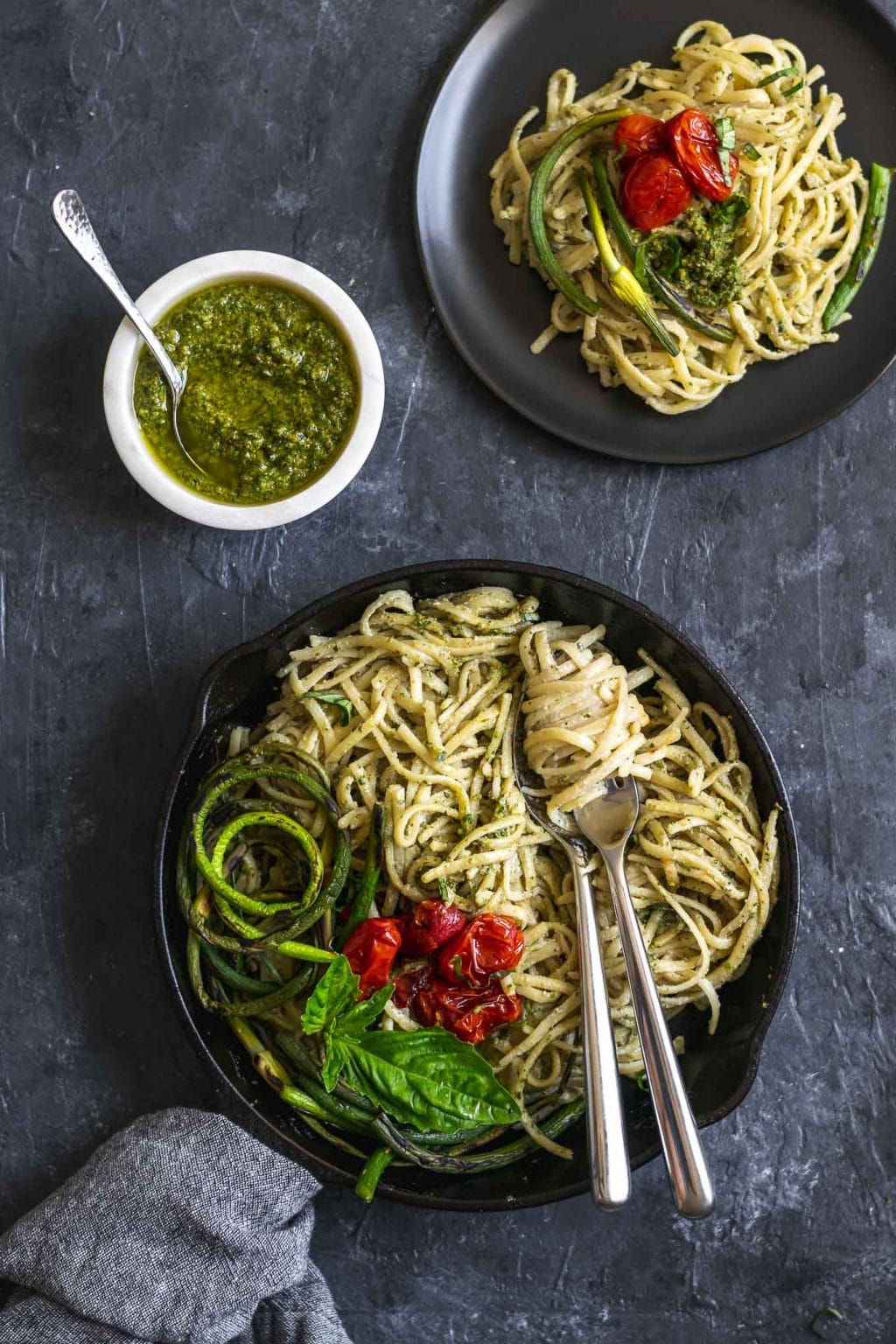 vegan garlic pesto alfredo pasta with grilled garlic scapes and roasted cherry tomatoes in a skillet with one plate served