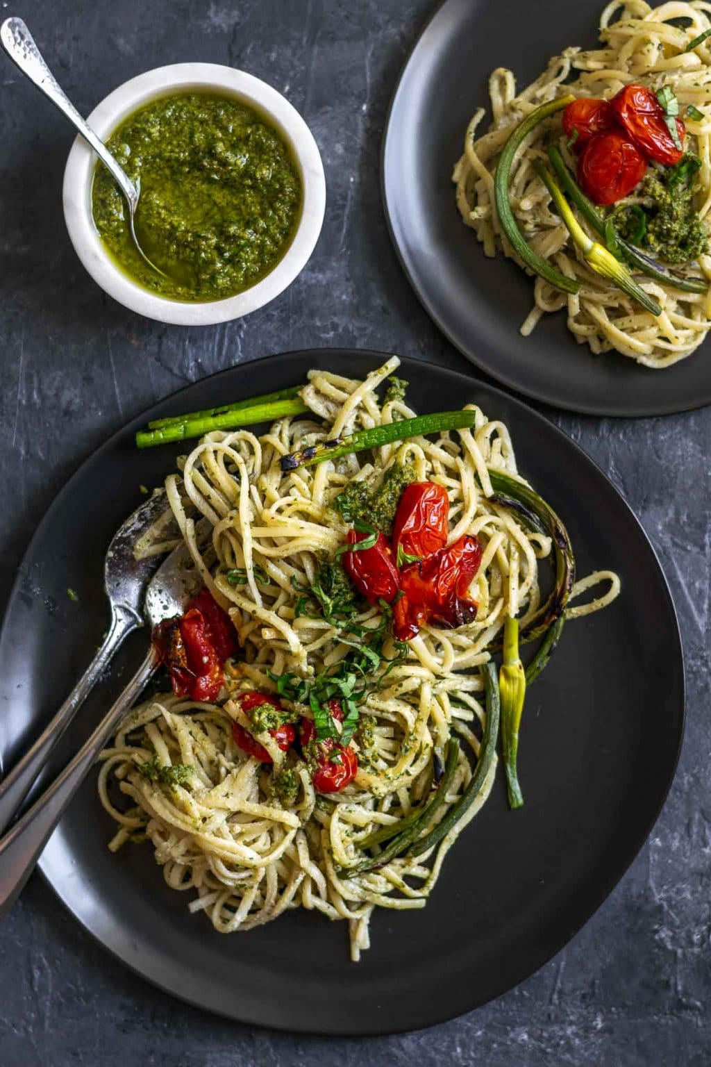 vegan garlic pesto alfredo pasta with grilled garlic scapes and roasted cherry tomatoes served on two plates with extra garlic scape pesto