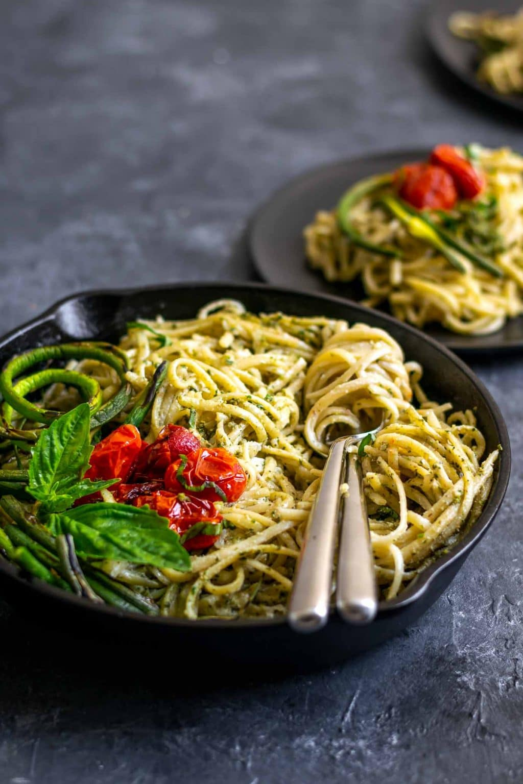 vegan garlic pesto alfredo pasta with grilled garlic scapes and roasted cherry tomatoes in a skillet with a couple of plates served