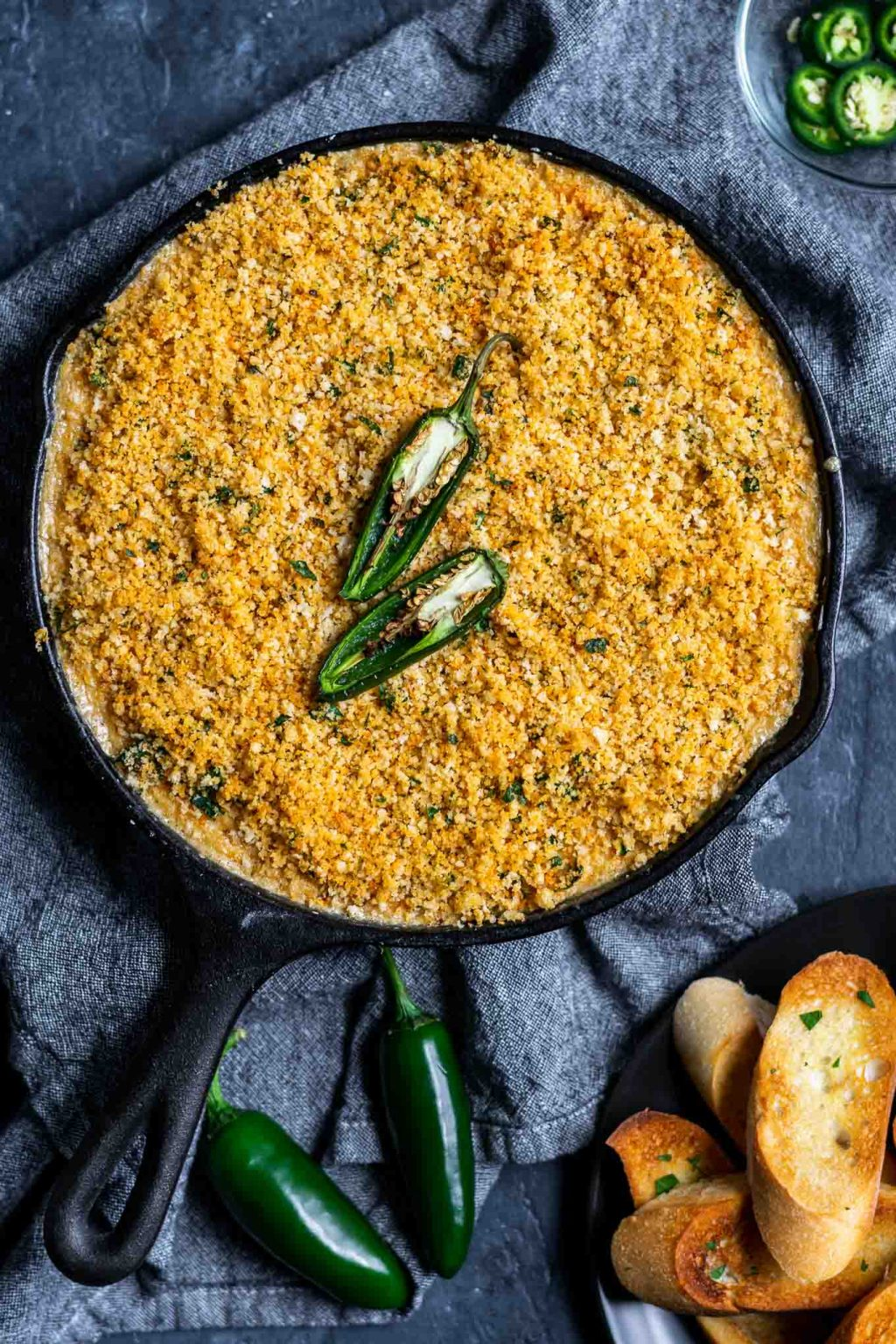 vegan jalapeño popper dip baked in cast iron with a bread crumb topping and served with crostini