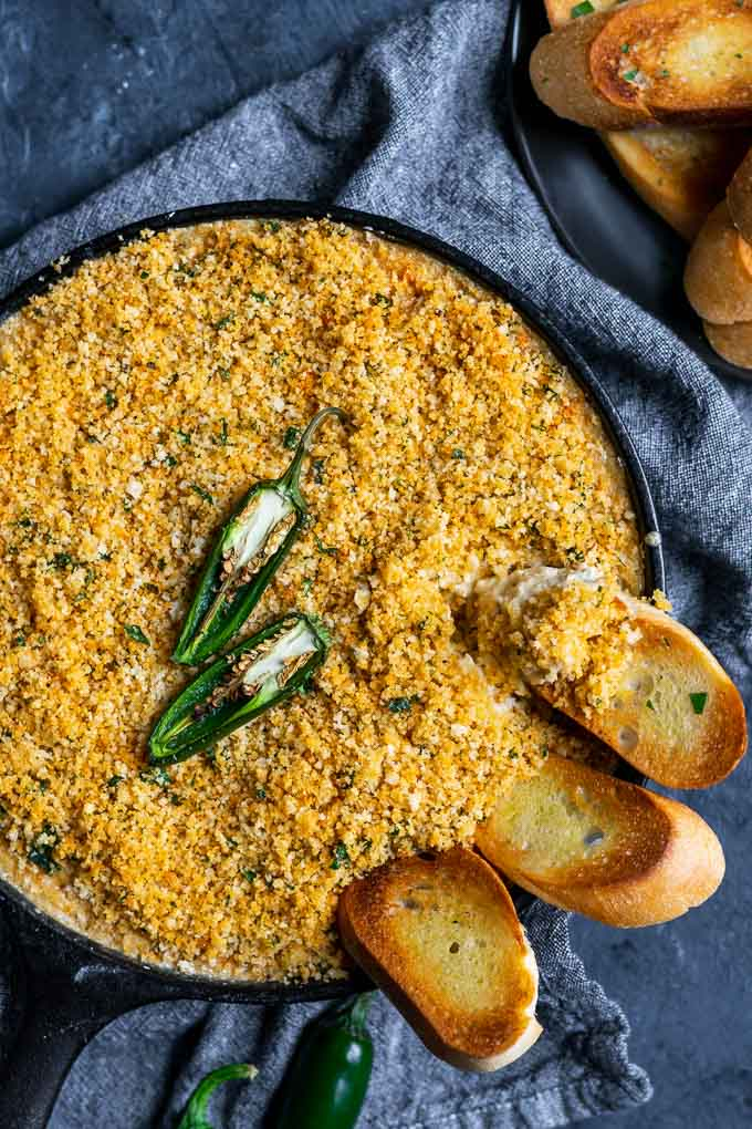 vegan jalapeño popper dip baked in a cast iron with a breadcrumb topping and crostini dipped into the pan
