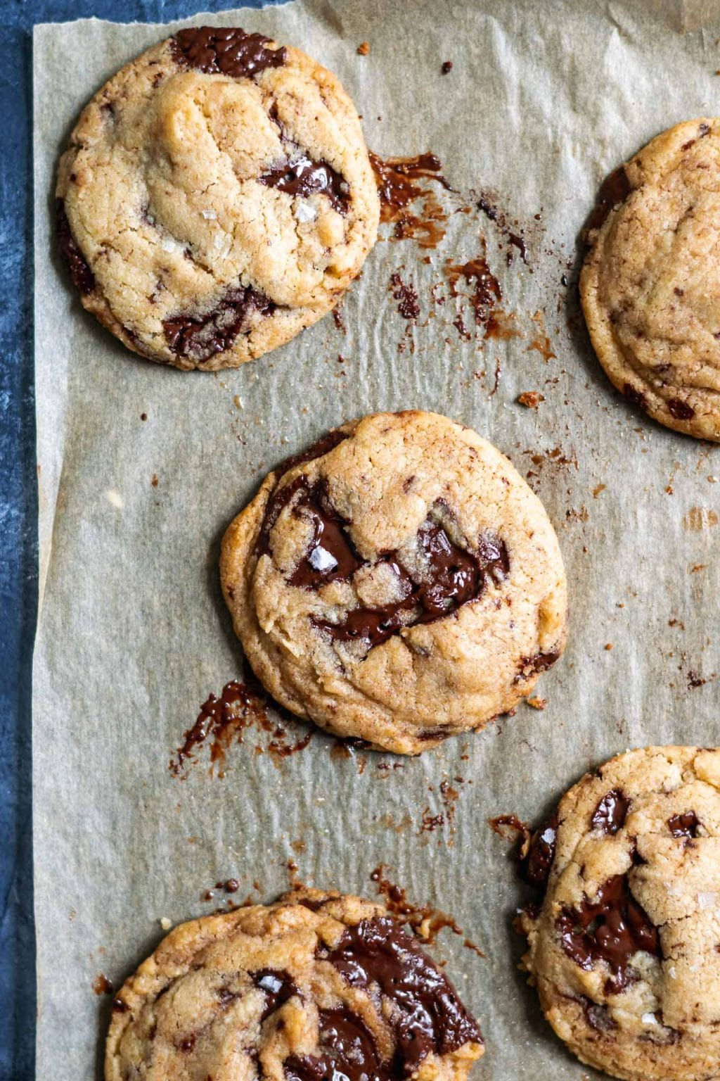 chewy vegan tahini chocolate chip cookies on a parchment paper