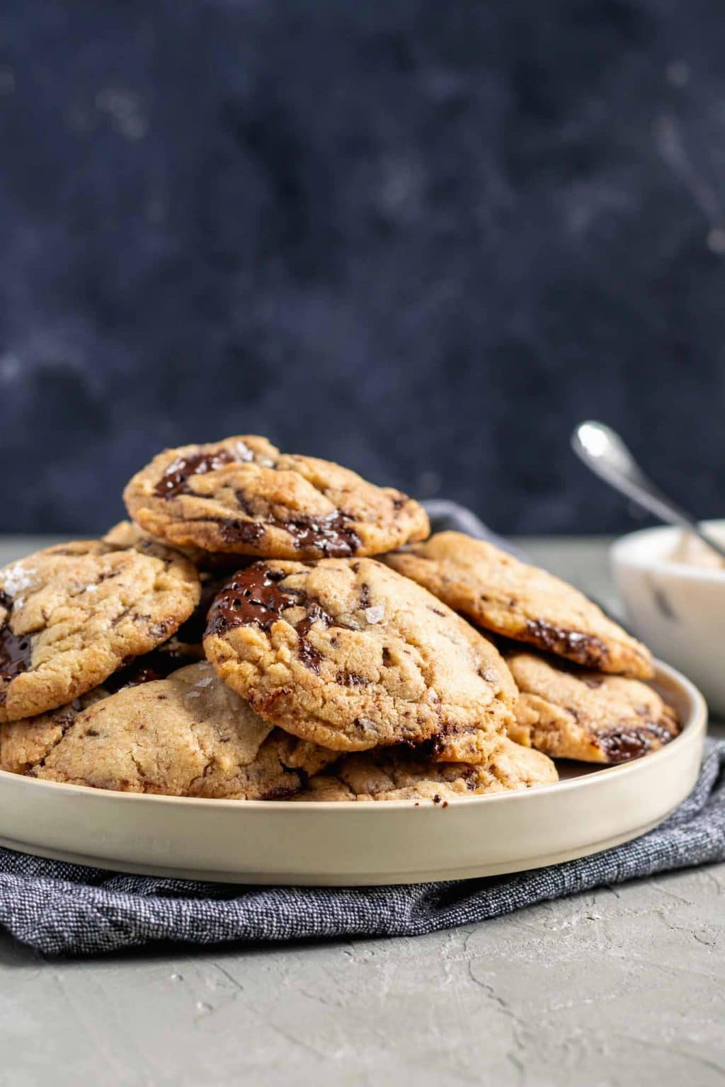 chewy vegan tahini chocolate chip cookies on a plate with a small bowl of tahini in the background