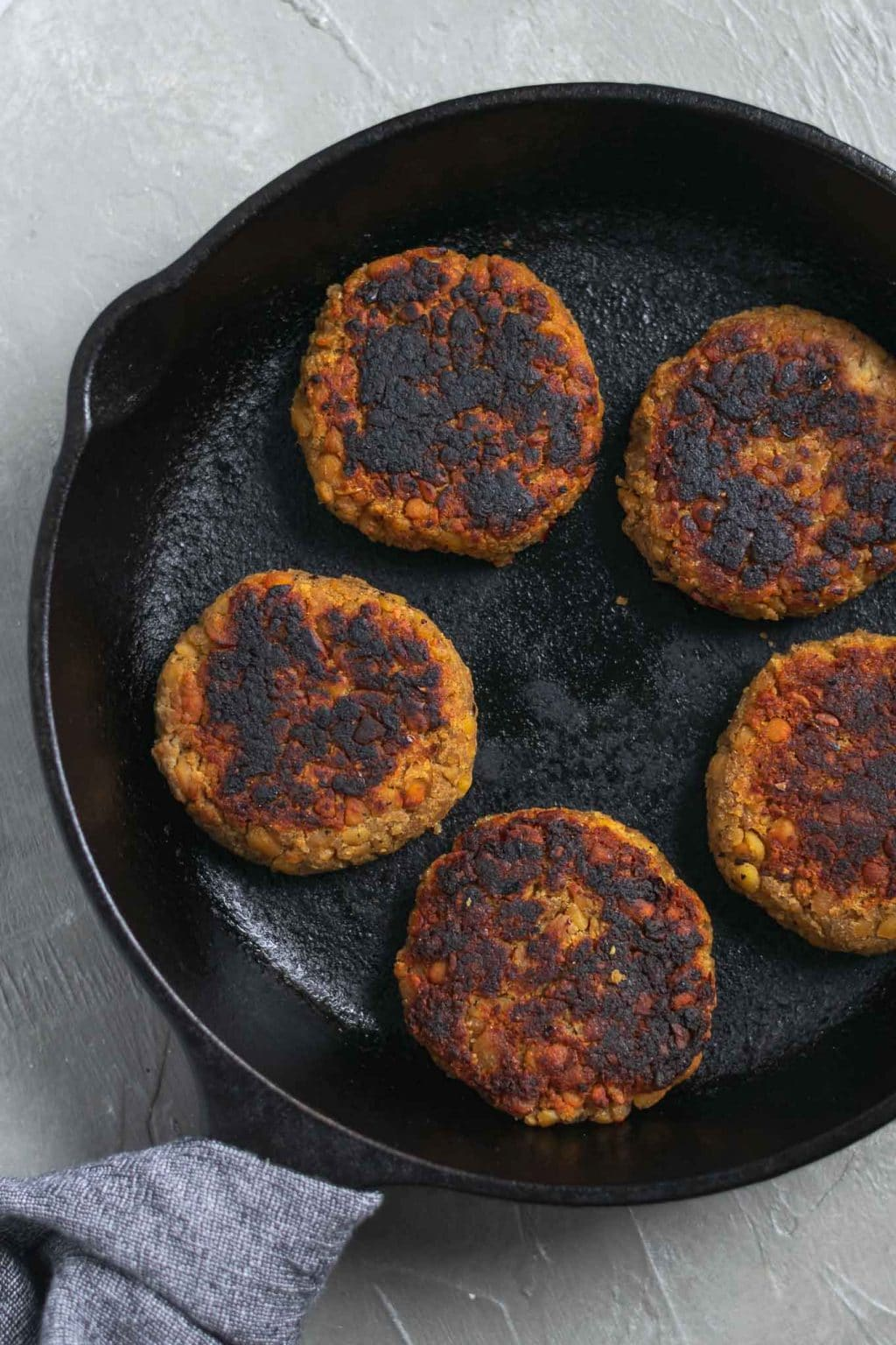 vegan tempeh maple breakfast sausage patties on a cast iron skillet