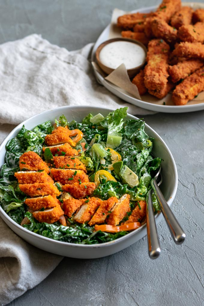 Crispy baked buffalo tofu wings with a romaine and avocado salad and vegan bleu cheese dressing. Additional plate of buffalo tofu wings on the side.
