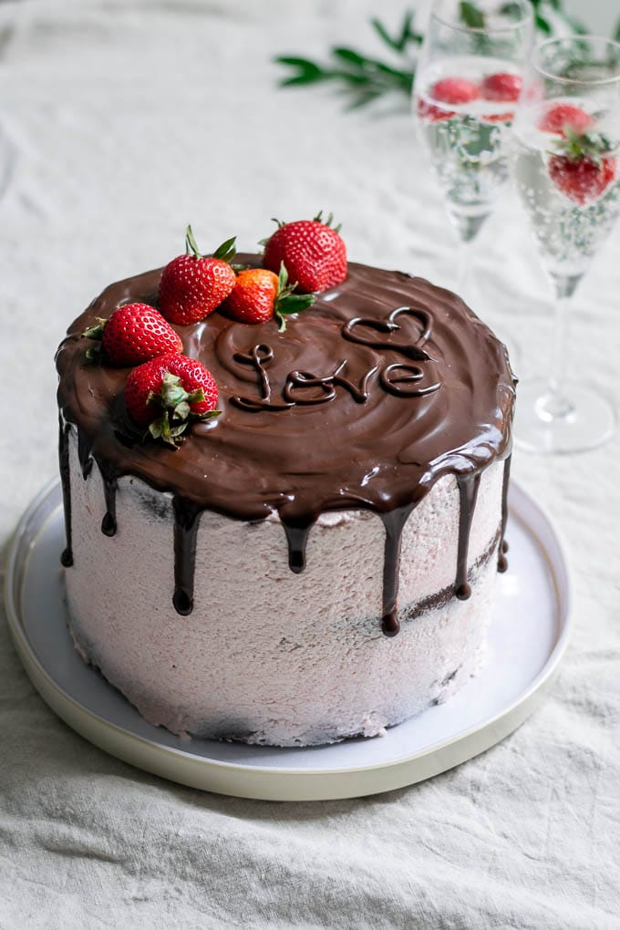 The ultimate easy vegan chocolate cake with strawberry Italian meringue buttercream, a chocolate drip, and fresh strawberries to decorate