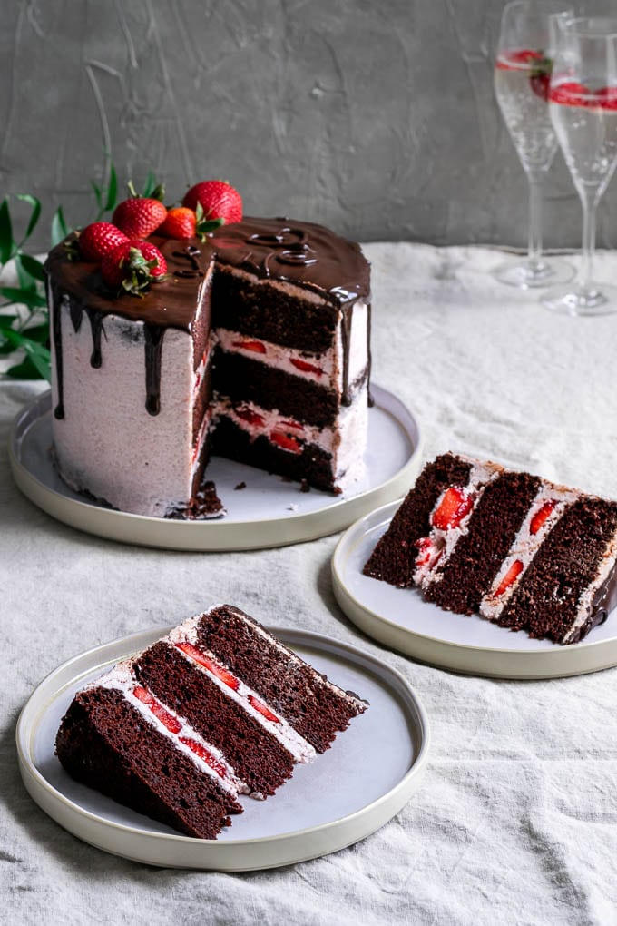 Two slices of the ultimate easy vegan chocolate cake with strawberry Italian meringue buttercream, a chocolate drip, and fresh strawberries to decorate
