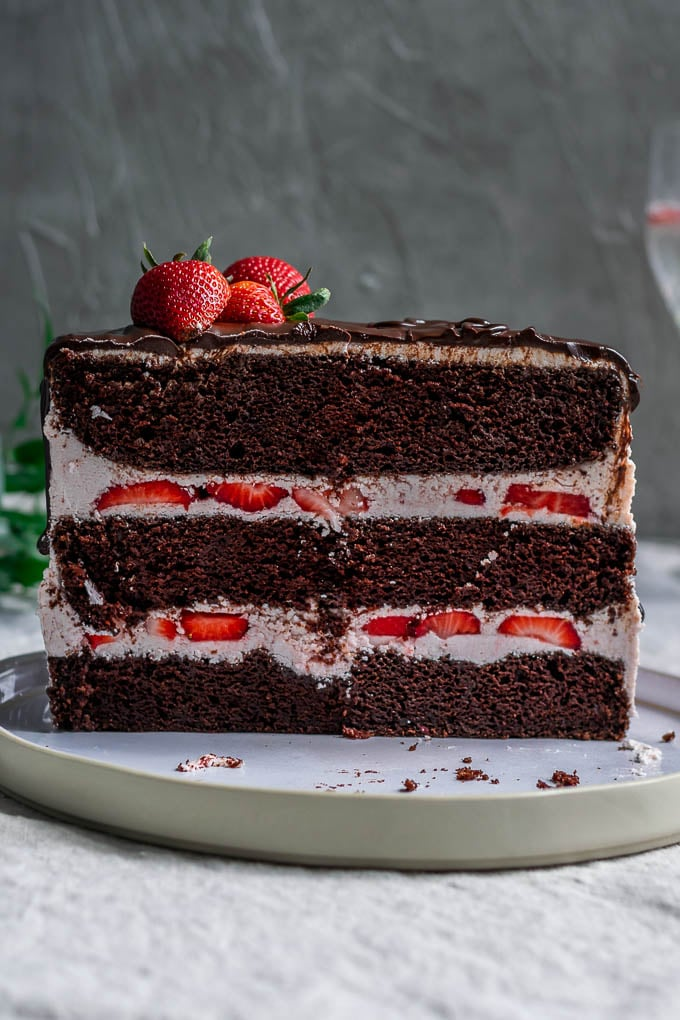 Cross section of the ultimate easy vegan chocolate cake with strawberry Italian meringue buttercream, a chocolate drip, and fresh strawberries to decorate